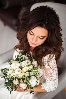 Portrait de la belle mariée bouchent maquillage de mariage et bouquet de mariée en mains