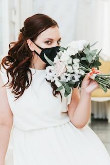 Portrait d'une belle mariée avec un bouquet dans un masque de protection médicale sur son visage. mariage pendant la période de pandémie covid-19.
