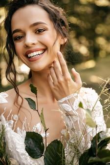 Portrait d'une belle mariée avec un bouquet de mariage sur fond de verdure