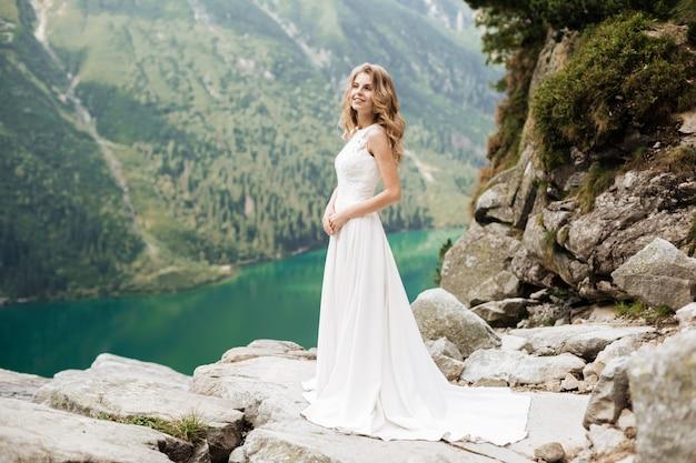 Portrait d'une belle mariée avec un bouquet de mariée. fille blonde aux cheveux bouclés et maquillage mode.