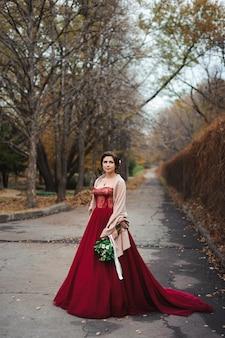 Portrait d'une belle mariée dans une robe rouge avec un bouquet