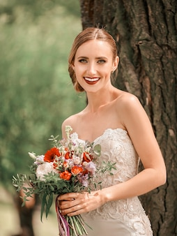 Portrait d'une belle mariée debout près d'un arbre dans un parc de la ville