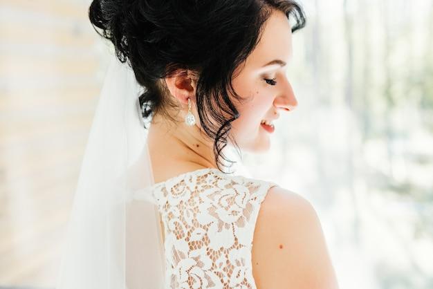 Portrait d'une belle mariée heureuse devant une fenêtre. préparations de mariage