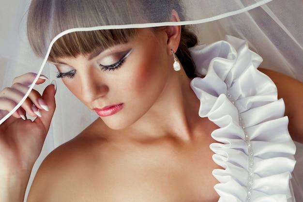 Portrait de la belle mariée magnifique avec le maquillage de mariage et la coiffure de mariage en robe de mariée