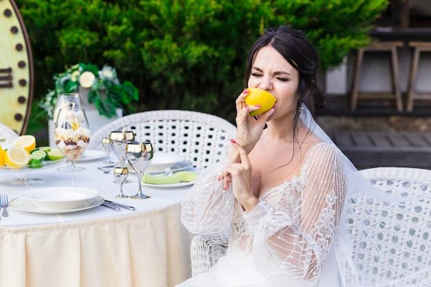 Portrait d'une belle mariée mangeant du citron lors d'une cérémonie de mariage.