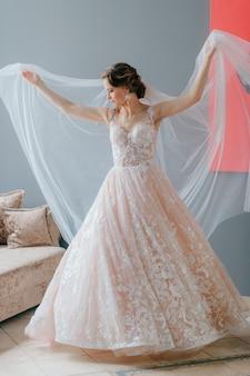 Portrait de la belle mariée en robe vintage blanche avec une fleur dans ses mains, posant sous le voile sur fond gris