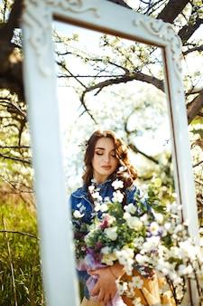 Portrait d'une belle mariée à travers le miroir. concept de mariage. mariage élégant. grande lumière du coucher du soleil. elle porte une veste bleue et une robe de mariée. jardin fleuri au printemps.