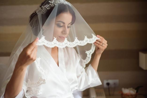 Portrait de la belle mariée avec voile de mode posant sur le lit au matin du mariage. maquillage. fille brune. voile de mariée.