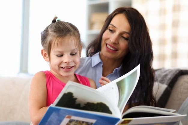 Portrait de belle mère et fille souriante lisant un livre intéressant.