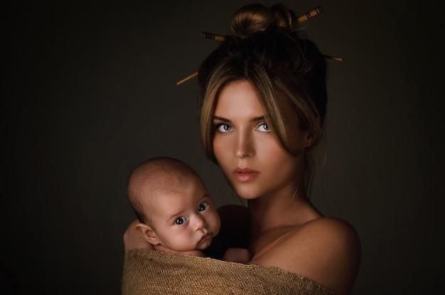 Portrait de la belle mère et son petit bébé sont enveloppés dans un sac