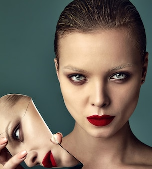 Portrait de la belle mode élégante femme brune modèle avec maquillage de soirée et lèvres rouges reflétant dans un miroir cassé sur bleu