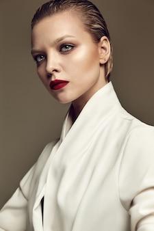 Portrait de la belle mode élégante femme brune modèle avec maquillage de soirée et lèvres rouges en veste blanche