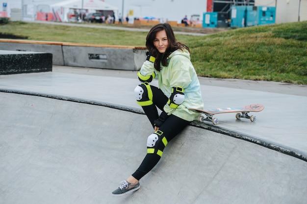 Portrait d'une belle patineuse souriante sur un pont. elle porte un équipement de protection. elle est appuyée sur sa main, regardant la caméra.