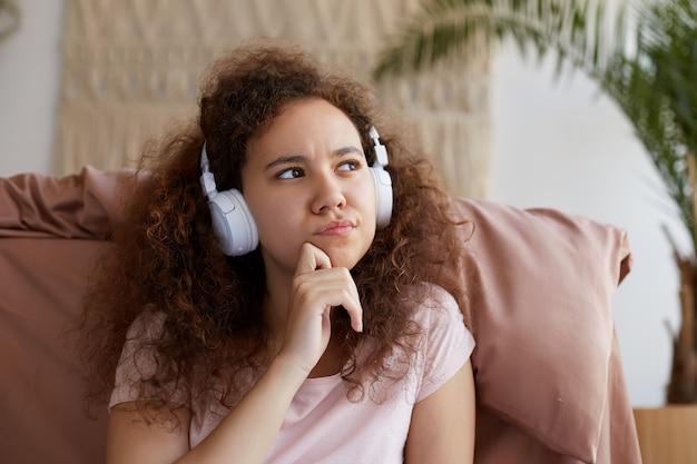 Portrait de belle pensée jeune femme afro-américaine aux cheveux bouclés assis dans la salle, écoutant la chanson préférée dans les écouteurs, regarde pensivement ailleurs