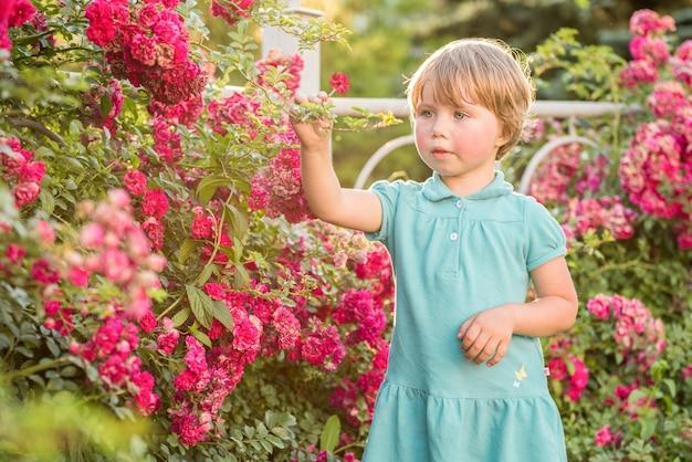 Portrait de la belle petite fille blonde avec des fleurs roses