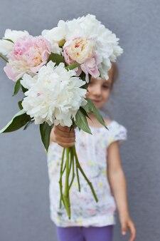 Portrait d'une belle petite fille avec un bouquet de pivoines