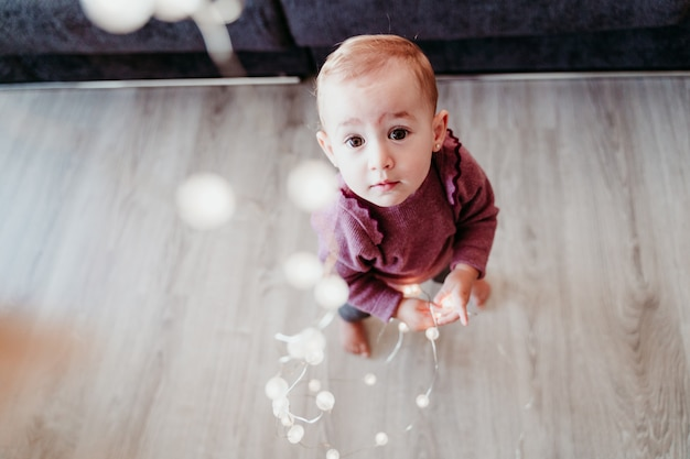 Portrait de la belle petite fille à la maison assis sur le canapé jouant avec une guirlande de lumières