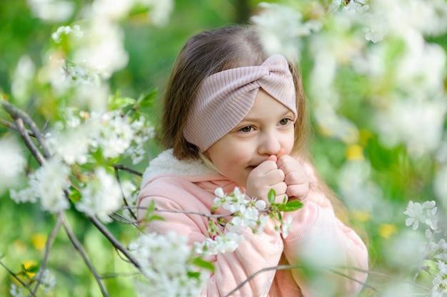 Portrait de belle petite fille près d'un cerisier en fleurs