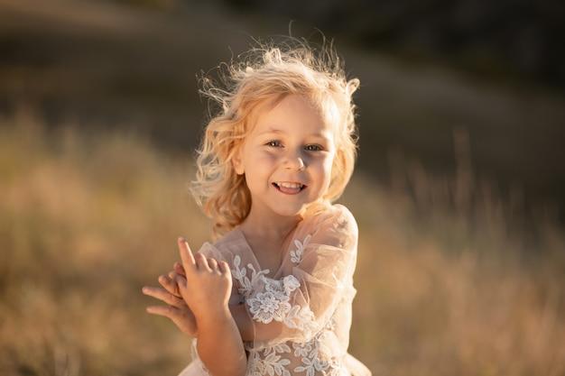 Portrait d'une belle petite fille princesse dans une robe rose. posant dans un champ au coucher du soleil