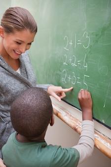 Portrait d'une belle prof et d'un élève faisant un ajout