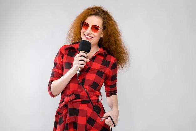 Portrait, de, belle rousse, heureux, jeune femme, à, lunettes soleil, avoirs, tenant microphone