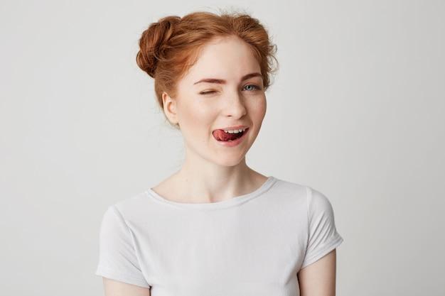 Portrait de la belle rousse souriante montrant la langue un clin de œil.