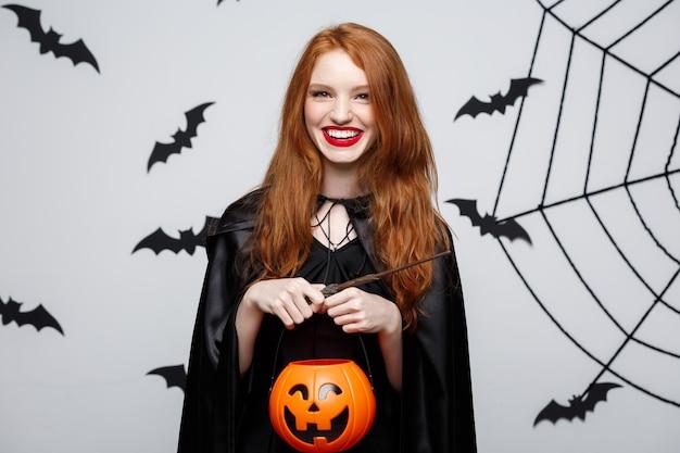 Portrait d'une belle sorcière caucasienne tenant une citrouille orange pour célébrer halloween.