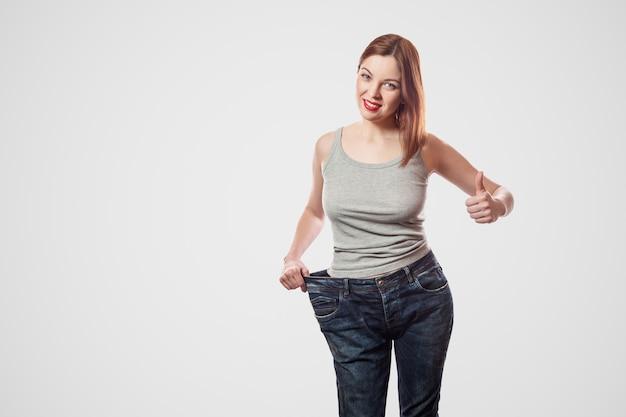 Portrait d'une belle taille mince heureuse de jeune femme en gros jeans et haut gris montrant une perte de poids réussie, intérieur, tourné en studio, isolé sur fond gris clair, concept de régime.