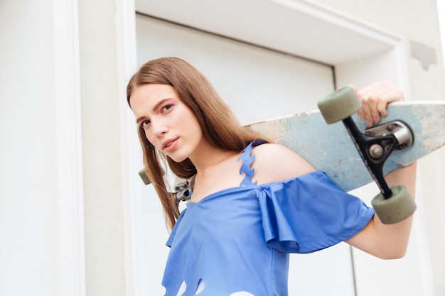 Portrait d'une belle teen girl holding skateboard sur fond blanc