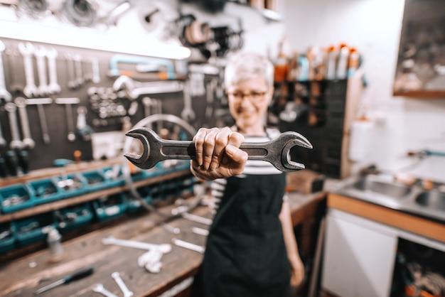 Portrait de la belle travailleuse de race blanche tenant une clé en se tenant debout dans l'atelier de vélo. mise au point sélective sur la clé.