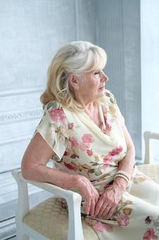 Portrait d'une belle vieille femme assise sur une chaise.