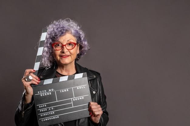 Portrait de la belle vieille femme tenant un battant de film sur un espace gris