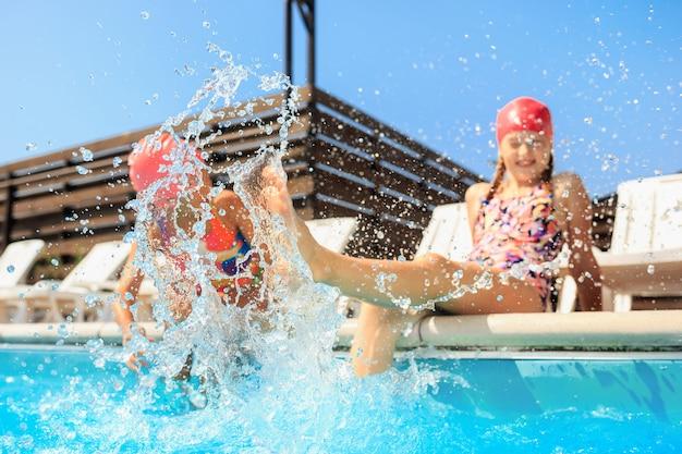 Le portrait de belles adolescentes souriantes au bord de la piscine