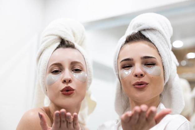 Portrait de belles filles européennes soufflant des baisers. jeunes femmes avec un cache-œil sur le visage et des serviettes de bain enveloppées sur la tête. concept de fête des filles. flou intérieur de la salle de bain dans un appartement moderne