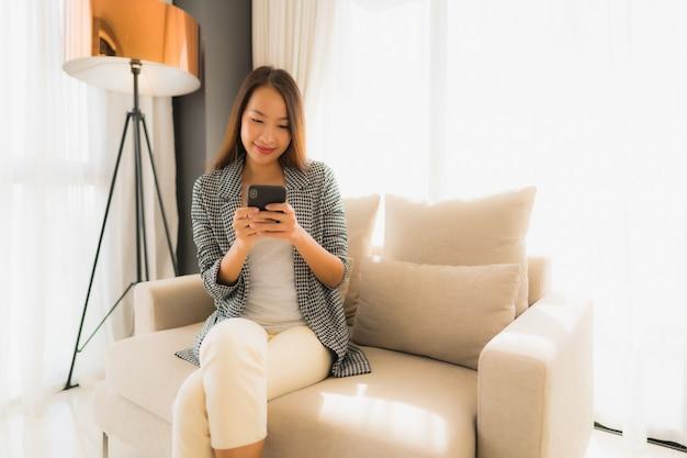 Portrait de belles jeunes femmes asiatiques à l'aide de téléphone portable parlant et assis sur une chaise canapé