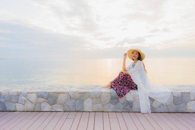 Portrait de belles jeunes femmes asiatiques sourire heureux se détendre autour de mer plage océan