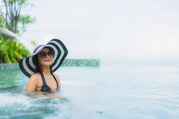 Portrait de belles jeunes femmes asiatiques sourire heureux se détendre piscine extérieure dans la station
