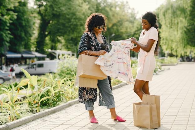 Portrait de belles jeunes femmes noires avec des sacs à provisions