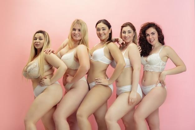 Portrait de belles jeunes femmes de taille plus posant sur rose