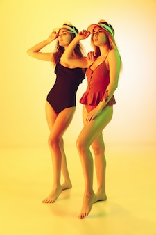 Portrait de belles jeunes filles isolé sur fond jaune studio en néon. femmes en body à la mode. expression faciale, été, week-end, beauté, concept de villégiature. vacances, jeunesse.