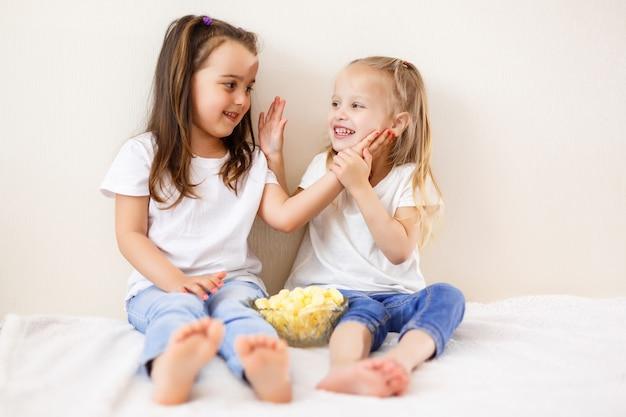 Portrait de belles jeunes soeurs mangeant des pop-corn à la maison.
