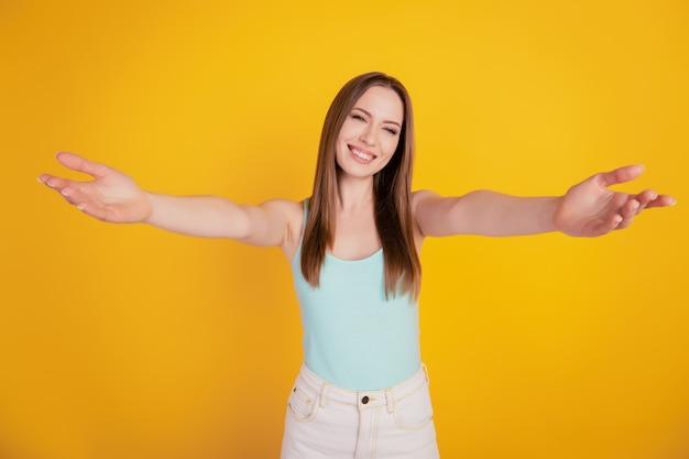 Portrait de belles et superbes bras étirés de dame amicale vous invitent à vous embrasser sur fond jaune