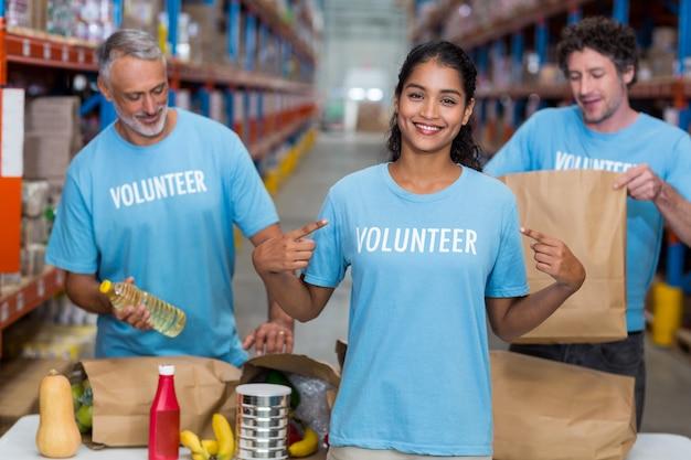 Portrait de bénévole pointant sur t-shirt
