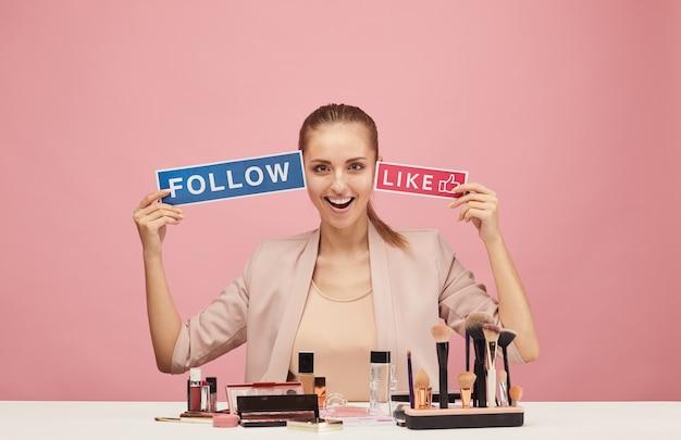 Portrait de blogueur beauté excité assis à la table avec des cosmétiques et souriant sur rose