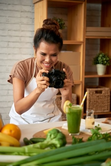 Portrait d'un blogueur culinaire prenant une photo du smoothie