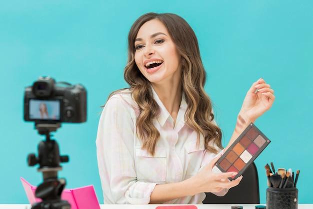 Portrait d'un blogueur essayant des produits de maquillage