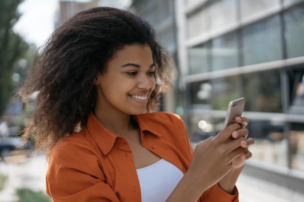 Portrait d'un blogueur prospère tenant un smartphone, vidéo en streaming en ligne. femme regardant des vidéos