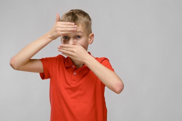 Portrait, de, blond, caucasien, triste, malade, petit garçon, dans, orange, t-shirt, fermeture, front, bouche, à, mains