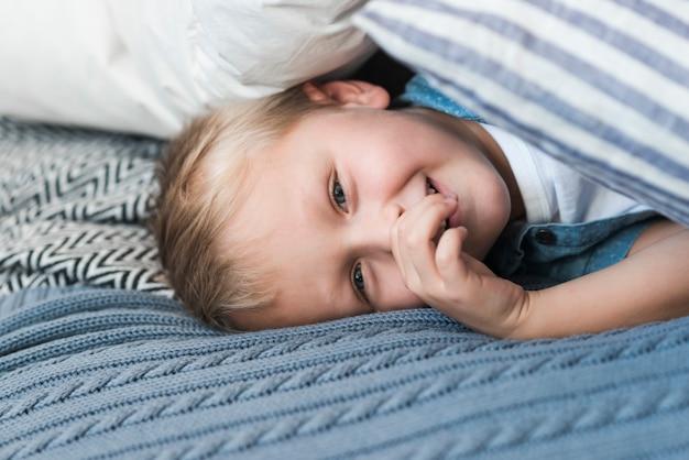 Portrait, de, blond, garçon, coucher lit, à, doigt, bouche