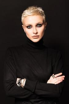 Portrait d'une blonde aux cheveux courts sur fond noir.